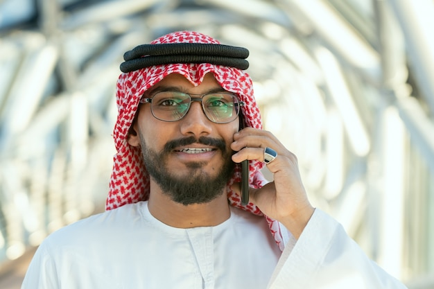 Sorridente giovane delegato arabo o uomo d'affari in abbigliamento nazionale che parla al telefono cellulare davanti alla telecamera in un business center contemporaneo