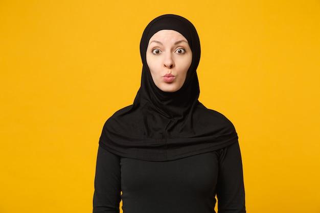Sorridente giovane donna musulmana araba in abiti neri hijab che soffia aria bacio, isolato sulla parete gialla, ritratto. concetto di stile di vita religioso della gente.