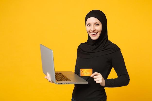 La giovane donna musulmana araba sorridente in vestiti neri di hijab tiene il pc del computer portatile, carta bancaria di credito isolata sul ritratto giallo della parete. concetto di stile di vita religioso della gente.