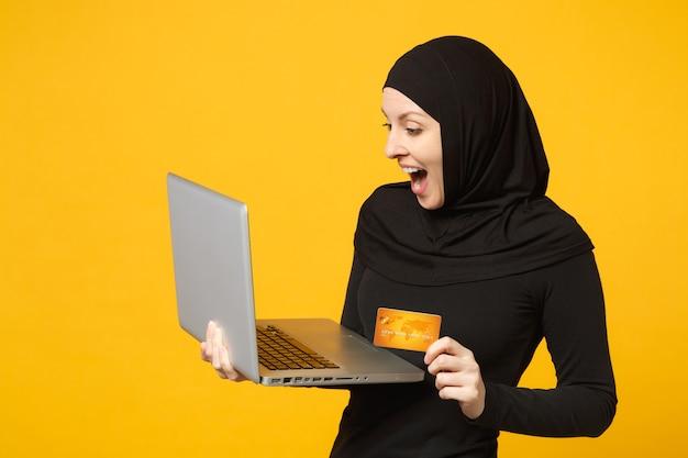 La giovane donna musulmana araba sorridente in vestiti neri di hijab tiene il pc del computer portatile, carta bancaria di credito isolata sul ritratto giallo della parete. concetto di stile di vita religioso della gente. Foto Premium