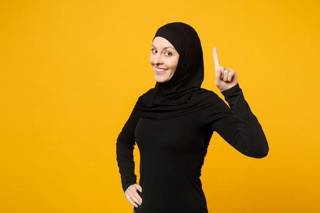 Sorridente giovane donna musulmana araba in abiti neri hijab che tiene il dito indice in alto con una grande nuova idea isolata sul muro giallo. concetto di stile di vita dell'islam religioso della gente.
