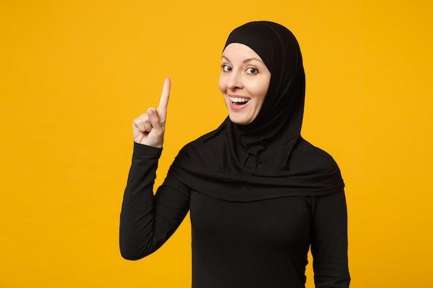 Sorridente giovane donna musulmana araba in abiti neri hijab che punta il dito verso l'alto, isolato sulla parete gialla, ritratto. concetto di stile di vita religioso della gente. mock up copia spazio