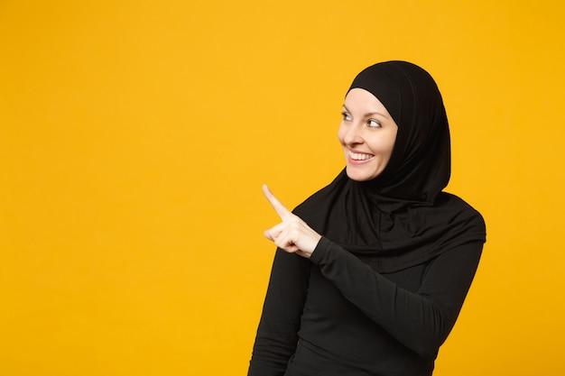 Sorridente giovane donna musulmana araba in abiti neri hijab che mostra lo spazio di puntamento della copia con il dito delle mani isolato sul ritratto giallo della parete. concetto di stile di vita religioso della gente.