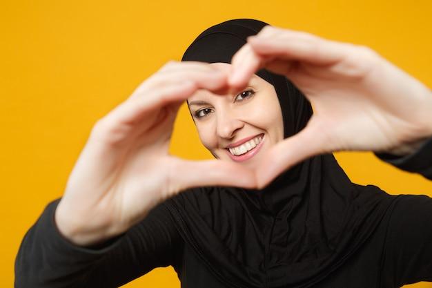 Sorridente giovane donna musulmana araba in abiti neri hijab che mostrano il cuore di forma con le mani isolate sulla parete gialla, ritratto. concetto di stile di vita religioso della gente.