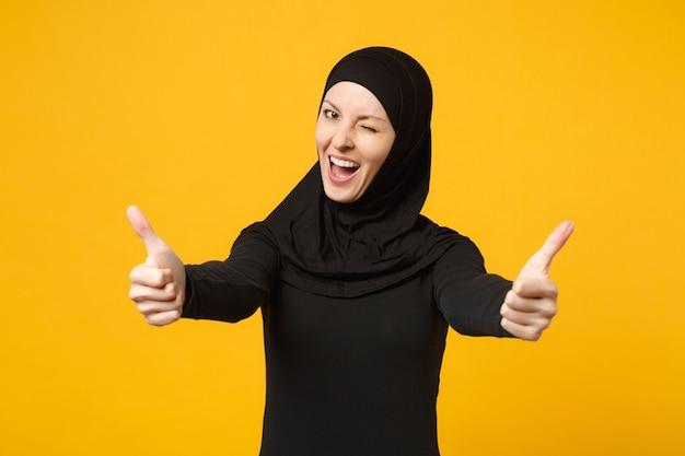 Sorridente giovane donna musulmana araba in abiti neri hijab che mostra i pollici in su, isolata sulla parete gialla, ritratto. concetto di stile di vita religioso della gente.