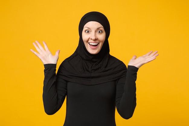 Sorridente giovane donna musulmana araba in abiti neri hijab allargando le mani, isolata sulla parete gialla, ritratto. concetto di stile di vita religioso della gente.