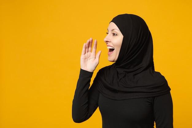 Sorridente giovane donna musulmana araba in abiti neri hijab sussurrando segreto dietro la sua mano isolata sul muro giallo, ritratto. concetto di stile di vita religioso della gente.