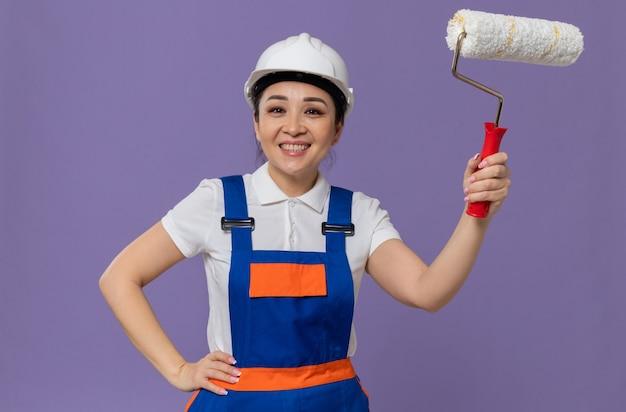 Sorridente giovane ragazza asiatica del costruttore con il casco di sicurezza bianco che mette la mano sulla sua vita e tiene il rullo di vernice