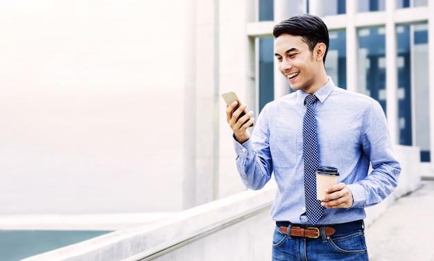 Sorridente giovane uomo d'affari asiatico utilizzando il telefono cellulare in città. stile di vita urbano moderno. ritratto maschile. mano che tiene la tazza di caffè. guardando smartphone