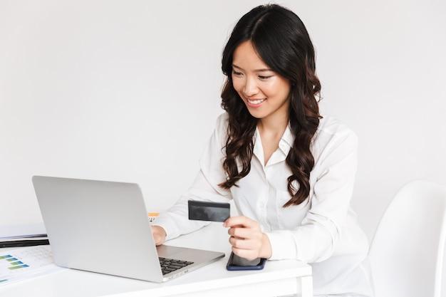 Giovane donna di affari asiatica sorridente che tiene la carta di credito di plastica
