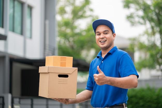 Una giovane consegna asiatica sorridente in uniforme blu con il pacco.