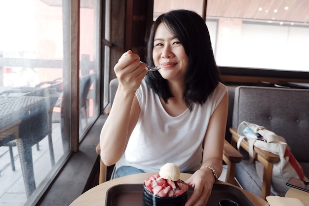 Sorridente giovane donna asiatica felice con il delizioso strawberry bingsu presso la caffetteria. stile di vita e relax della donna d'affari in vacanza concept