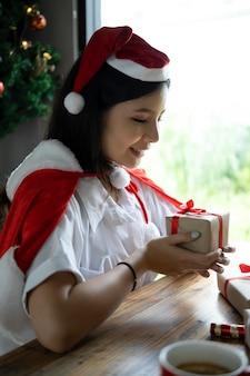 Sorridente giovane donna asiatica in cappello della santa che tiene il contenitore di regalo di natale.