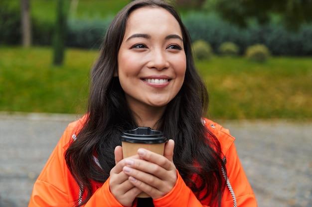 Sorridente giovane donna asiatica che indossa un impermeabile che cammina all'aperto sotto la pioggia, tenendo in mano una tazza di caffè, guardando lontano