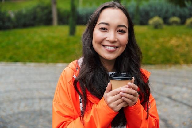 Sorridente giovane donna asiatica che indossa un impermeabile che cammina all'aperto sotto la pioggia, tenendo in mano una tazza di caffè
