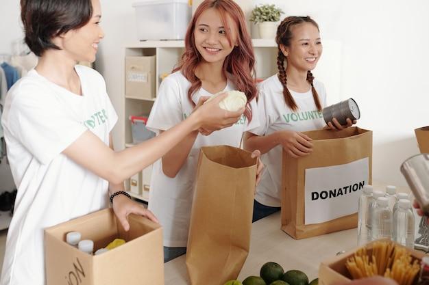 Giovani donne asiatiche sorridenti che confezionano cibo in scatola, frutta, verdura e acqua in confezioni di carta da donare in un centro di beneficenza