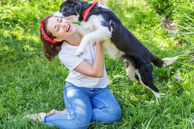 Giovane donna attraente sorridente che gioca con il border collie sveglio del cucciolo di cane nel parco della città o del giardino