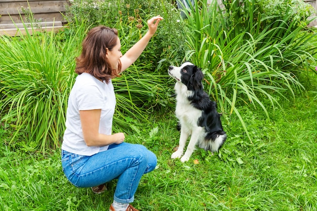 Sorridente giovane donna attraente che gioca con il grazioso cucciolo di cane border collie in giardino