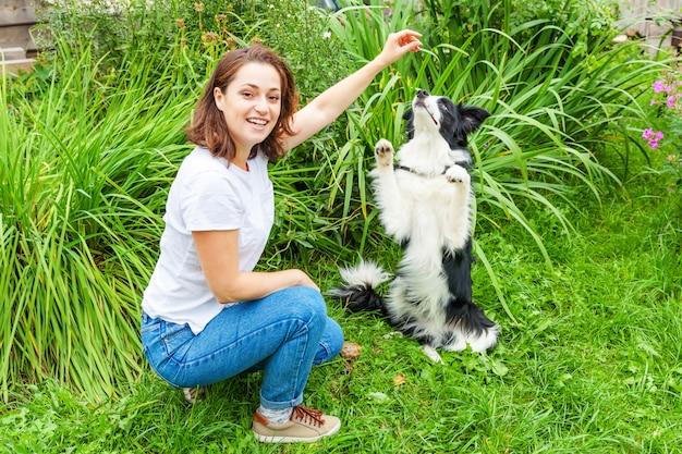 La giovane donna attraente sorridente che gioca con il cucciolo di cane sveglio border collie nel giardino dell'estate o la città parcheggia il fondo all'aperto. trucco di addestramento della ragazza con l'amico cane. cura degli animali e concetto di animali.