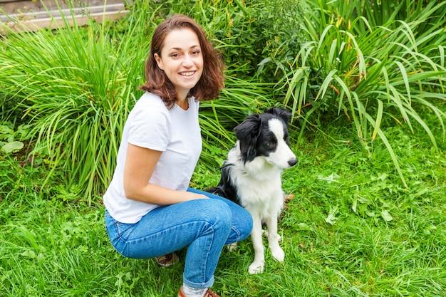 Giovane donna attraente sorridente che gioca con il border collie sveglio del cucciolo di cane nel parco del giardino o della città di estate all'aperto. trucco di addestramento della ragazza con l'amico cane. cura degli animali e concetto di animali.
