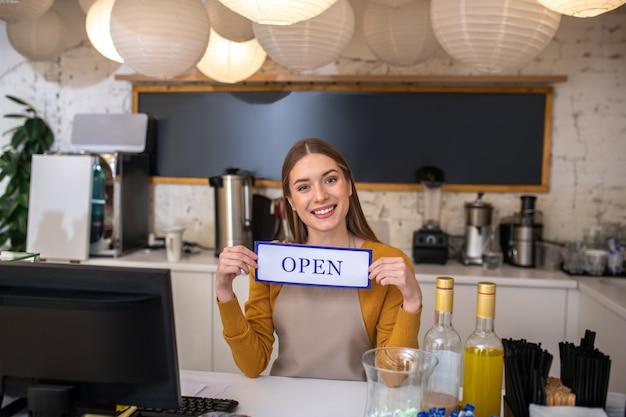 Un giovane barista sorridente che tiene il segno aperto