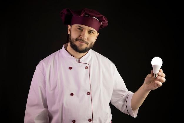 Sorridente giovane chef barbuto in uniforme che tiene la lampadina a risparmio energetico