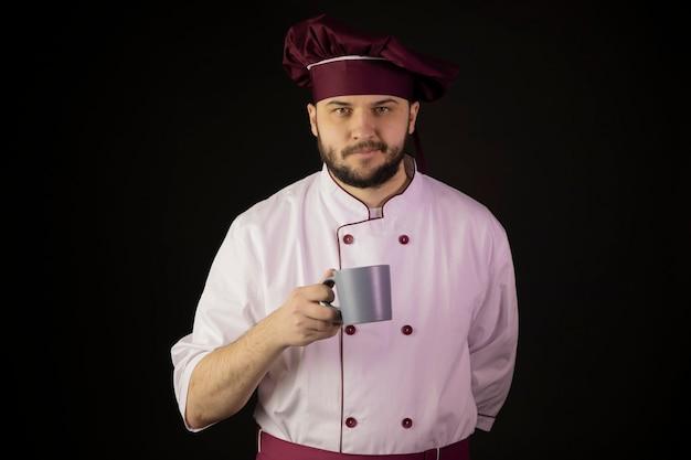 Sorridente giovane chef maschio barbuto in uniforme tenendo la tazza di caffè in mano