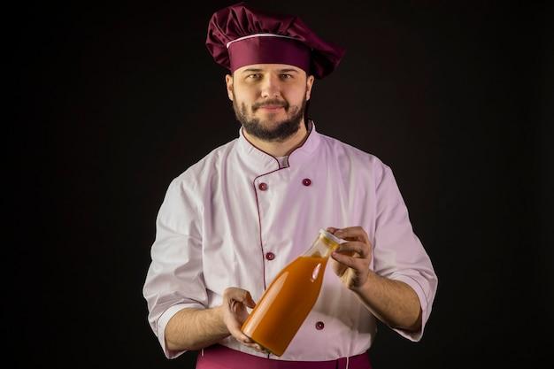 Sorridente giovane chef maschio barbuto in uniforme che tiene la bottiglia di plastica di succo di frutta