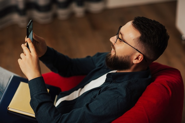 Sorridente giovane uomo barbuto con gli occhiali utilizza lo smartphone. sta guardando un video divertente.