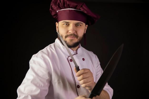 Sorridente giovane chef barbuto in uniforme tiene coltelli affilati incrociati