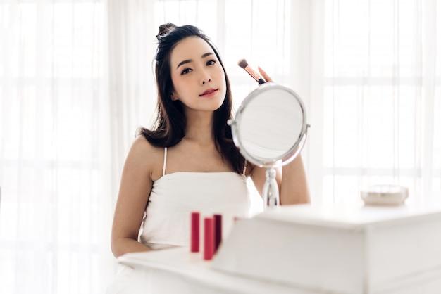 La pelle sana fresca sorridente della giovane bella donna asiatica che guarda sullo specchio e che tiene le spazzole di trucco con i cosmetici ha messo a casa