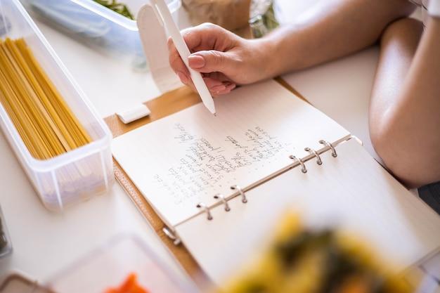 Sorridente giovane bella donna d'affari che prende appunti in un diario di carta in una moderna cucina in stile nordico