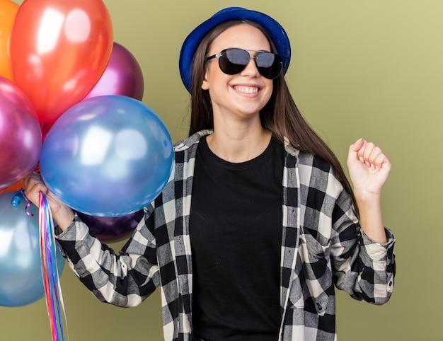 Sorridente giovane bella ragazza che indossa un cappello blu con gli occhiali che tengono palloncini che mostrano sì gesto isolato sulla parete verde oliva