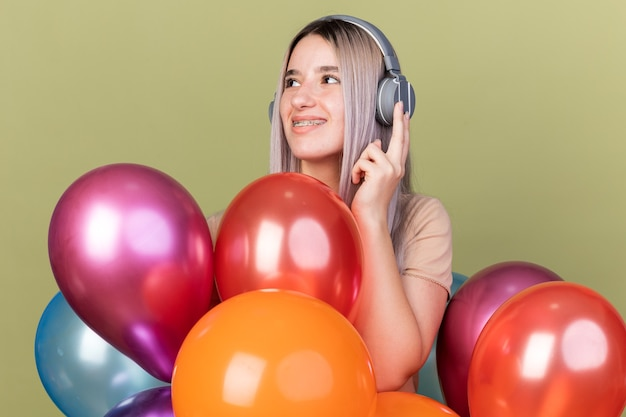 Sorridente giovane bella ragazza che indossa bretelle dentali con le cuffie in piedi dietro palloncini isolati su parete verde oliva