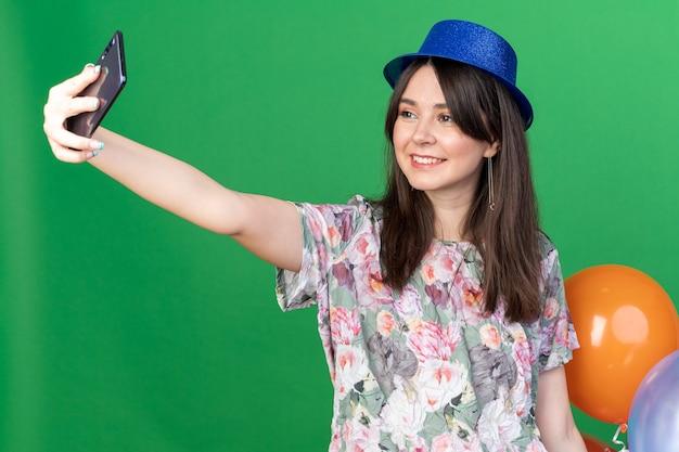 La giovane bella ragazza sorridente che indossa il cappello del partito che tiene i palloni prende un selfie