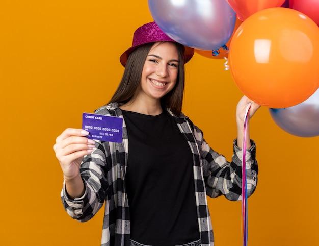 Sorridente giovane bella ragazza che indossa cappello da festa tenendo palloncini con carta di credito isolata sulla parete arancione