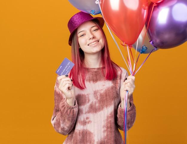 Sorridente giovane bella ragazza che indossa un cappello da festa in possesso di palloncini con carta di credito