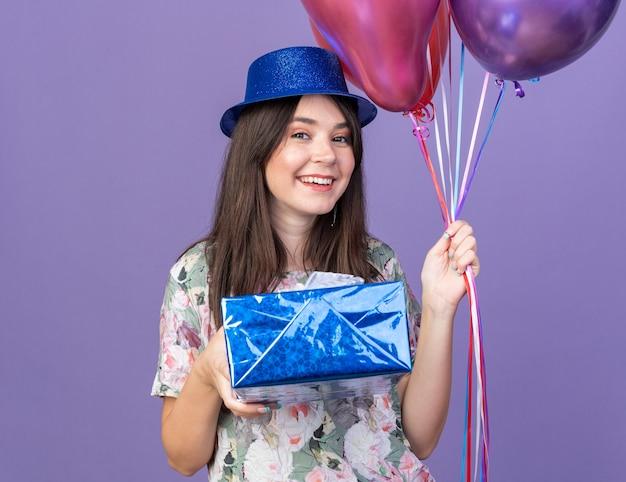 Sorridente giovane bella ragazza che indossa cappello da festa che tiene palloncini con scatola regalo isolata sulla parete blu