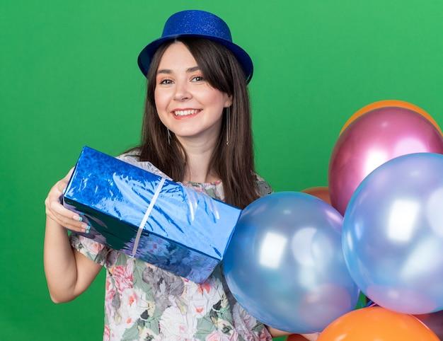 Sorridente giovane bella ragazza che indossa un cappello da festa con palloncini con scatola regalo