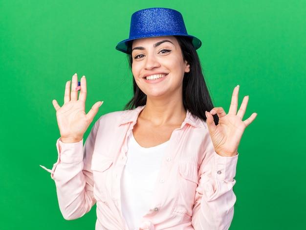 Sorridente giovane bella ragazza che indossa cappello da festa tenendo il fischio di festa che mostra gesto ok isolato sul muro verde