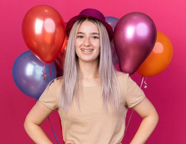 Sorridente giovane bella ragazza che indossa un cappello da festa in piedi di fronte a palloncini che mettono le mani sull'anca isolata sulla parete rosa