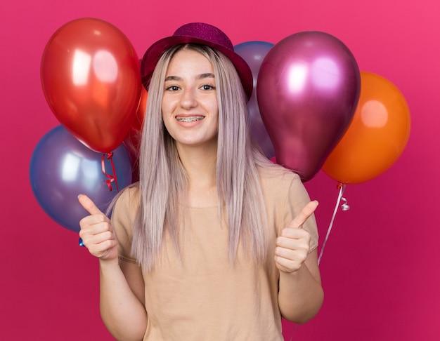 Sorridente giovane bella ragazza che indossa un cappello da festa in piedi davanti a palloncini che mostrano i pollici in su isolati sulla parete rosa