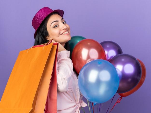 Sorridente giovane bella ragazza che indossa un cappello da festa in piedi palloncini vicini che tengono la borsa regalo sulla spalla