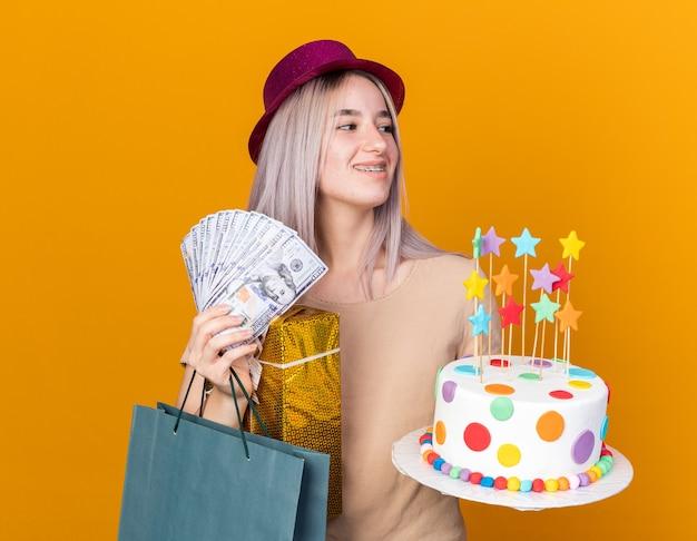 Sorridente giovane bella ragazza che indossa cappello da festa con bretelle in possesso di contanti e torta con regali isolati su parete arancione