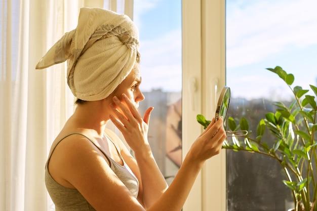 Sorridente giovane bella donna da vicino a casa vicino alla finestra con maschera facciale di frutta naturale fatta in casa di kiwi sul viso, asciugamano sulla testa. cura della pelle, cosmetici, cosmetologia, dermatologia.