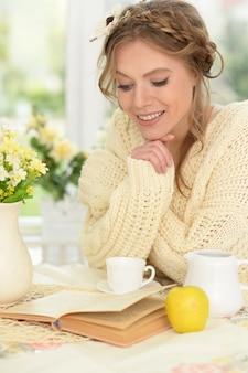 Sorridente giovane bella donna che beve il tè con il libro in cucina