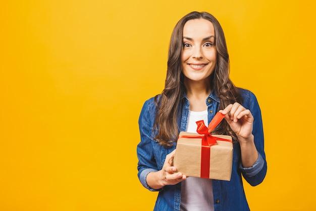 La giovane bella donna sorridente tiene il contenitore di regalo rosso