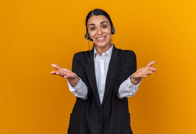Sorridente giovane bella donna che indossa un blazer nero con auricolare