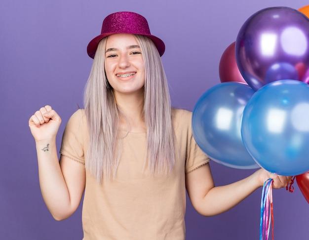 Sorridente giovane bella donna che indossa bretelle dentali e cappello da festa che tiene palloncini che mostrano sì gesto isolato su parete blu