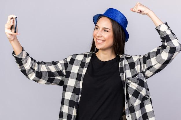 Sorridente giovane bella donna che indossa un cappello da festa che fa un gesto forte, scatta un selfie isolato sul muro bianco